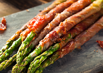 Prosciutto Wrapped Asparagus on marble cutting board